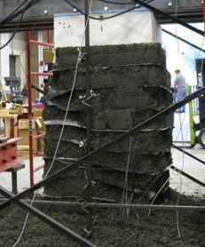 Side view of pier failure for a geosynthetic reinforced soil performance test. Layers are slumped and loose aggregate is strewn on the floor of the test facility. A shallow shear failure plane is shown throughout the composite. A reaction assembly is shown around the pier with a concrete footing on top of the pier.