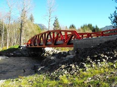 This is a photo of the Sunday Creek geosynthetic reinforced soil integrated bridge system with a red-type truss structure in King County, Washington. The bridge crosses a creek and is protected by rip rap.
