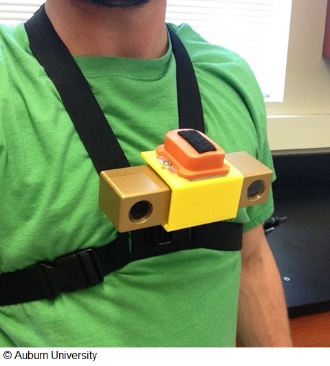 A close-up photo of a man in a green t-shirt wearing a chest-mounted device.