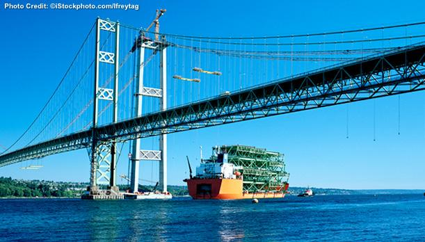 A suspension bridge with two spans is shown, and a ship is seen under the bridge.