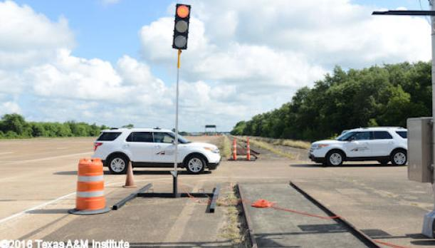 Photo shows two white mid-sized SUVs approaching a railroad crossing on a test track.